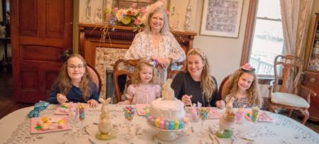 Woman poses behind a family of four female guests decorating cookies at a spring tea party