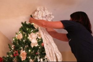 A woman putting a ribbon bow on top of a Christmas tree