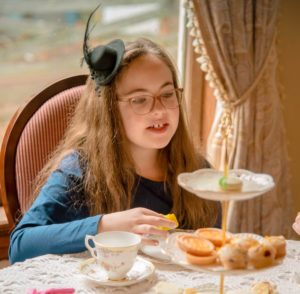 Young girl in blue dress with black fascinator enjoys snacks from a tiered tea tray