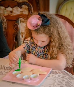 Young girl with long curly hair wearing a colorful dress enjoys petite fours at a formal tea.