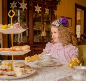 Young girl with curly hair, pink dress and yellow elbow gloves taking tea.