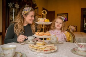 Young mother wearing dark gray and small child in a pink dress enjoy formal tea treats.