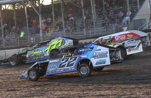 Three multi-colored race cars zooming along on a dirt track