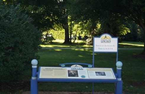 Green grass, shrubs, and trees with a sign and information table about Abraham Lincoln