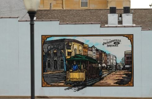 Hand painted mural of old downtown Jacksonville Square and a trolley on the side wall of a white building