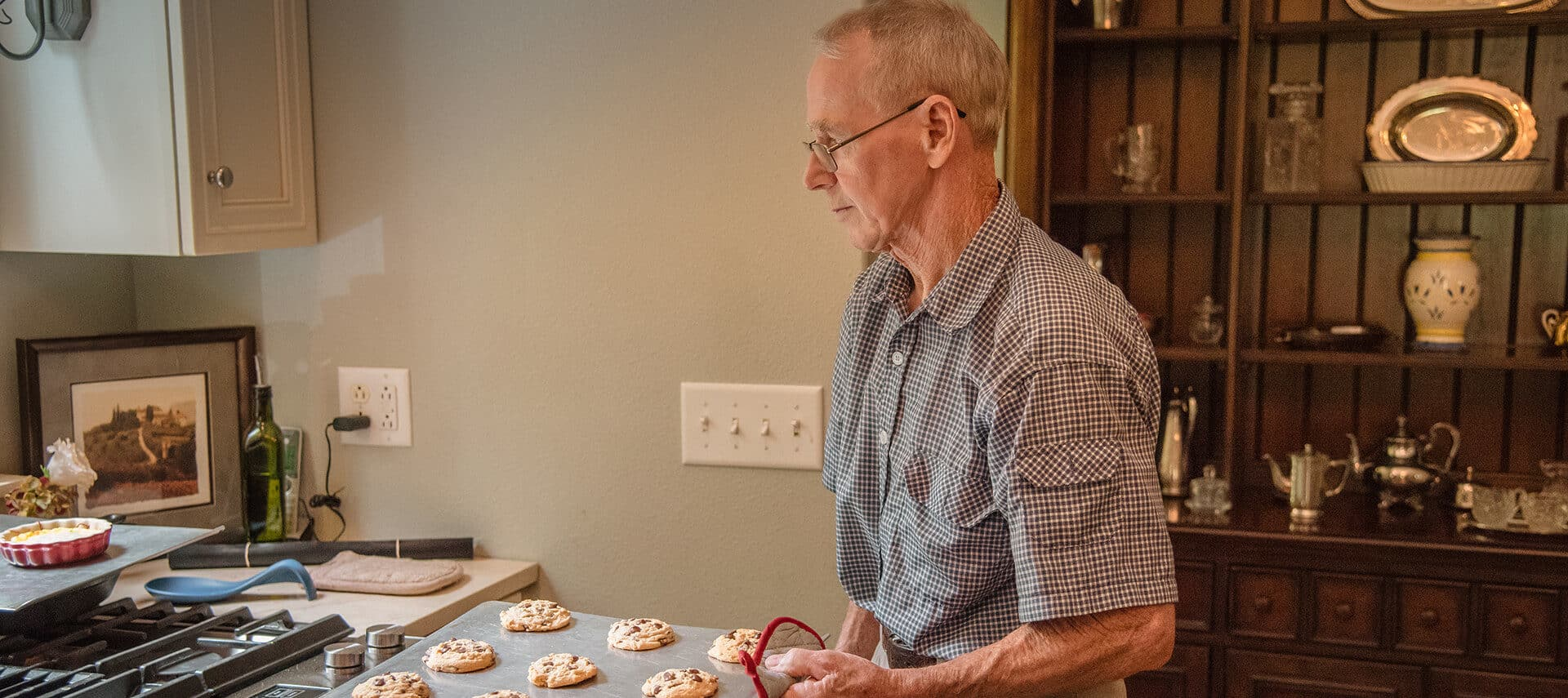 man holding hot cookie tray