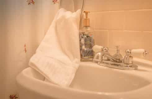 bathroom sink with chrome fixtures white towel and- iquid hand soap