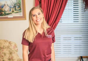 blond-woman-with-a-big-smile-wearing-a-burgundy-polo-shirt