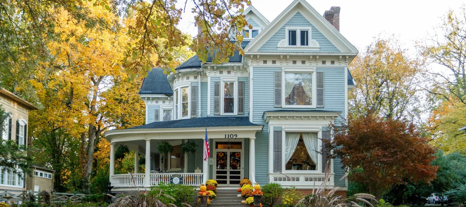 Blue Victorian home surrounded by colorful trees