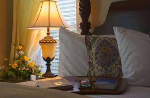 Close up view of pillows and wooden tray with books on top all on top of a bed