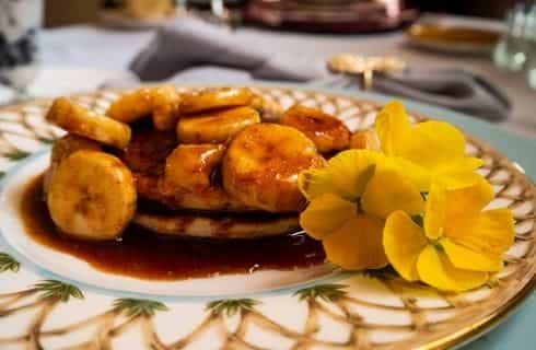 Close up view of breakfast dish with bananas and pancakes with yellow flowers on the side as a decoration