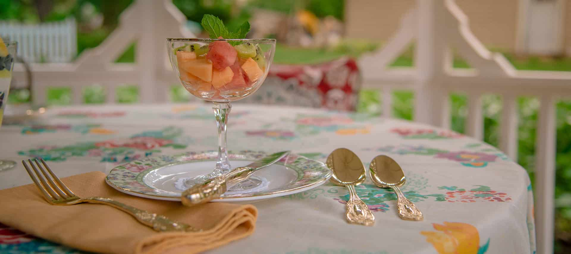 fresh melon and cantaloupe in stemmed glass on plate with gold utensils