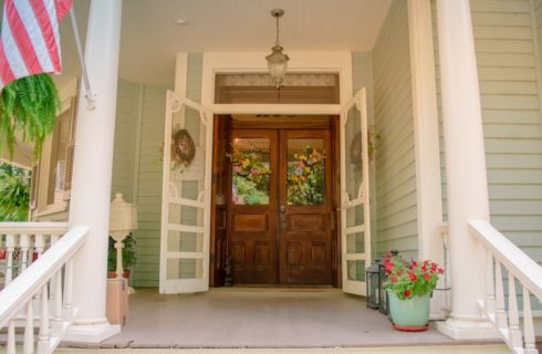 Exterior view of property's wooden front door and side of front porch