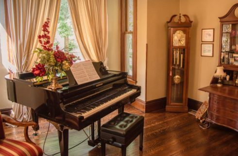 Large room with hardwood flooring, black piano, wooden furniture, and upholstered ornate chair