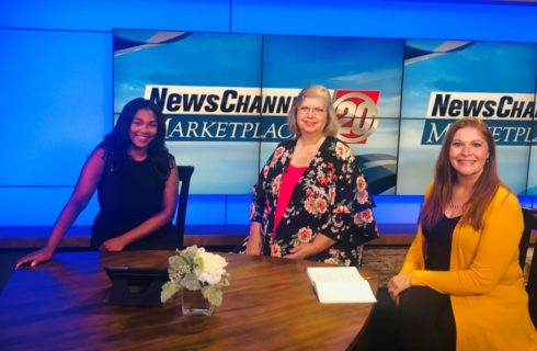 Three ladies in dresses, sitting around a wooden table on a local news station's set