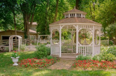 White wooden gazeebo surrounded by green grass, green shrubs, and red flowers