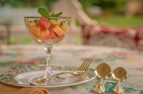 Close up view of cut fresh fruit in tall glass goblet on fine china plate