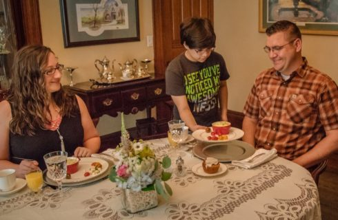 Couple sitting at dining table while host serves a plate of food