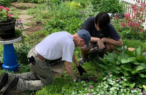 Man and woman standing in green grass near a beautiful flower garden