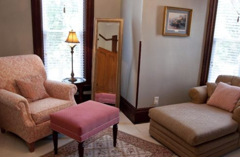 Bedroom with sitting area that includes an upholstered arm chair and stool and chaise lounge chair