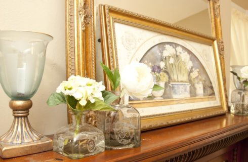 Ornate wooden mantel with decorations, large frame, and framed print on top