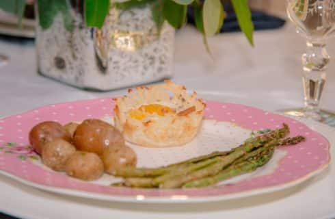 Close up view of a breakfast dish with an egg, potatoes, and asparagus on a white and pink polka dot fine china plate