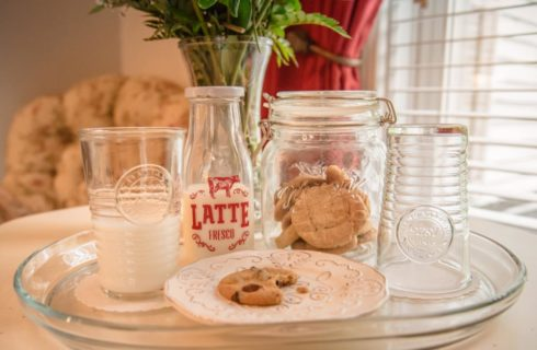 Close up view of glass tray with glasses filled with milk, a jar filled with cookies, and a small plate with a chocolate chip cookie