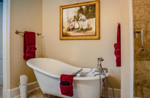 Large white clawfoot tub, tiled flooring, and red towels hanging on the tub and towel bars