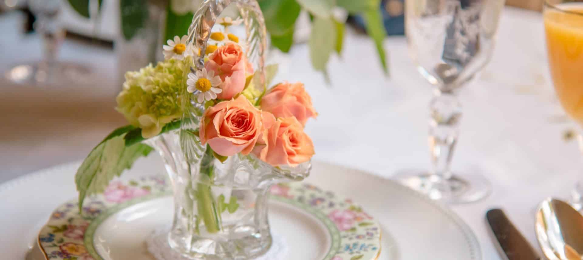 Small glass basket filled with peach roses and white daisies sitting on top of fine china