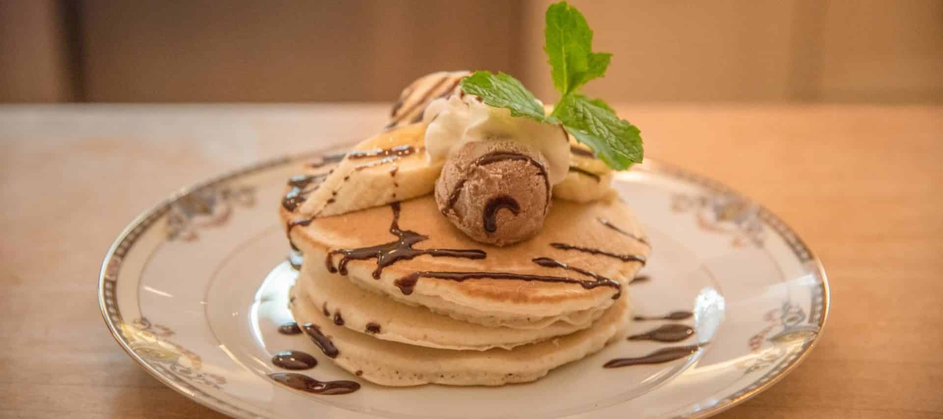 Close up view of a large stack of pancakes with sliced bananas, chocolate drizzle, and mint sprig