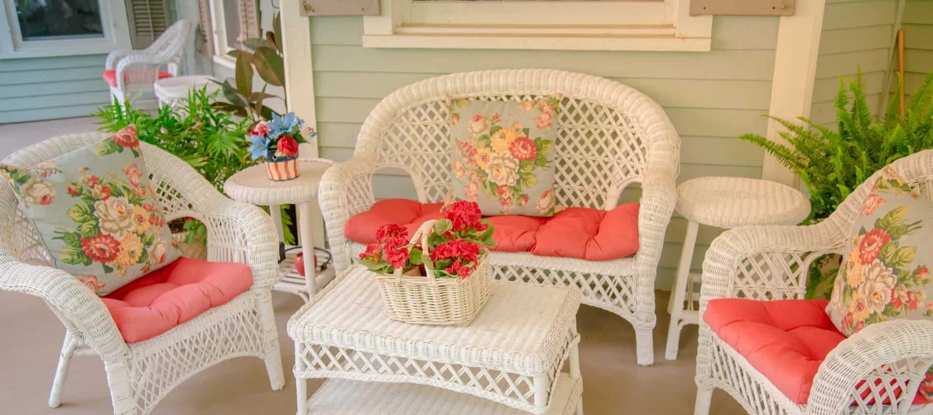 White wicker patio furniture with coral and floral cushions and pillows on front porch