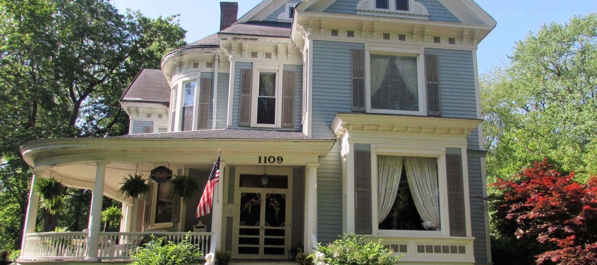Front exterior view of the property painted blue and white with dark shutters, wrap around porch, American flag, and surrounded by green trees