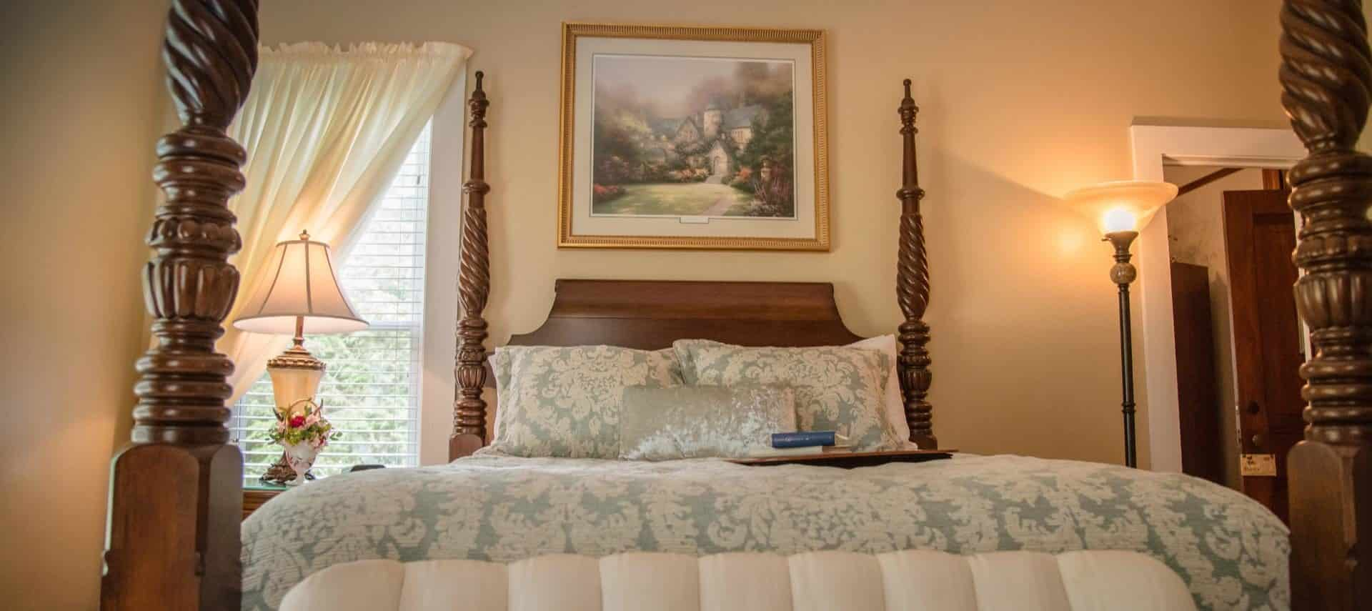 Bedroom with cream walls, dark wooden four-post bed, and white and gray bedding