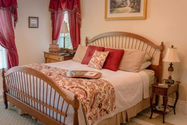 Bedroom with cream walls, wooden furniture and bed, white and tan bedding, and red curtains