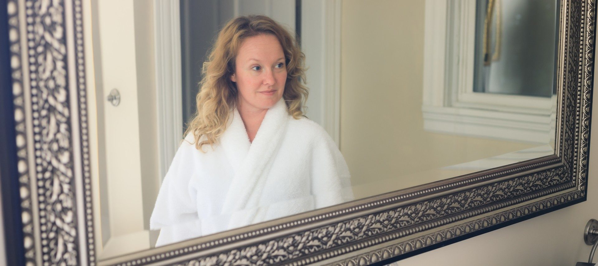 beautiful blond woman in white robe reflection in framed mirror