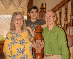 mom son and dad pose together on a Victorian staircase