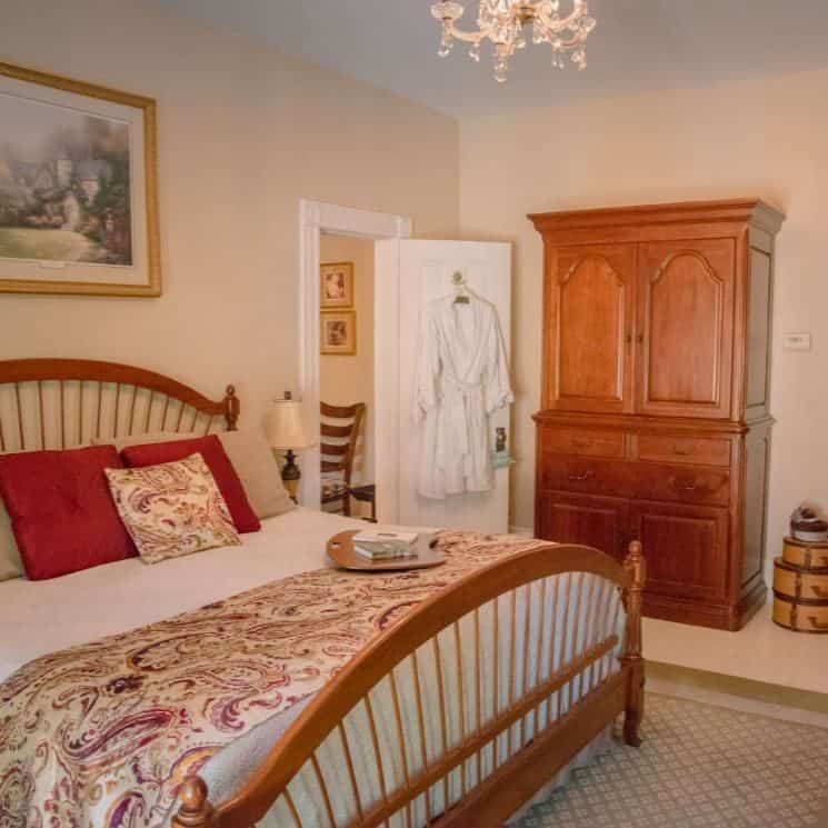 Bedroom with cream walls, wooden furniture and bed, white bedspread, and white robe hanging on door