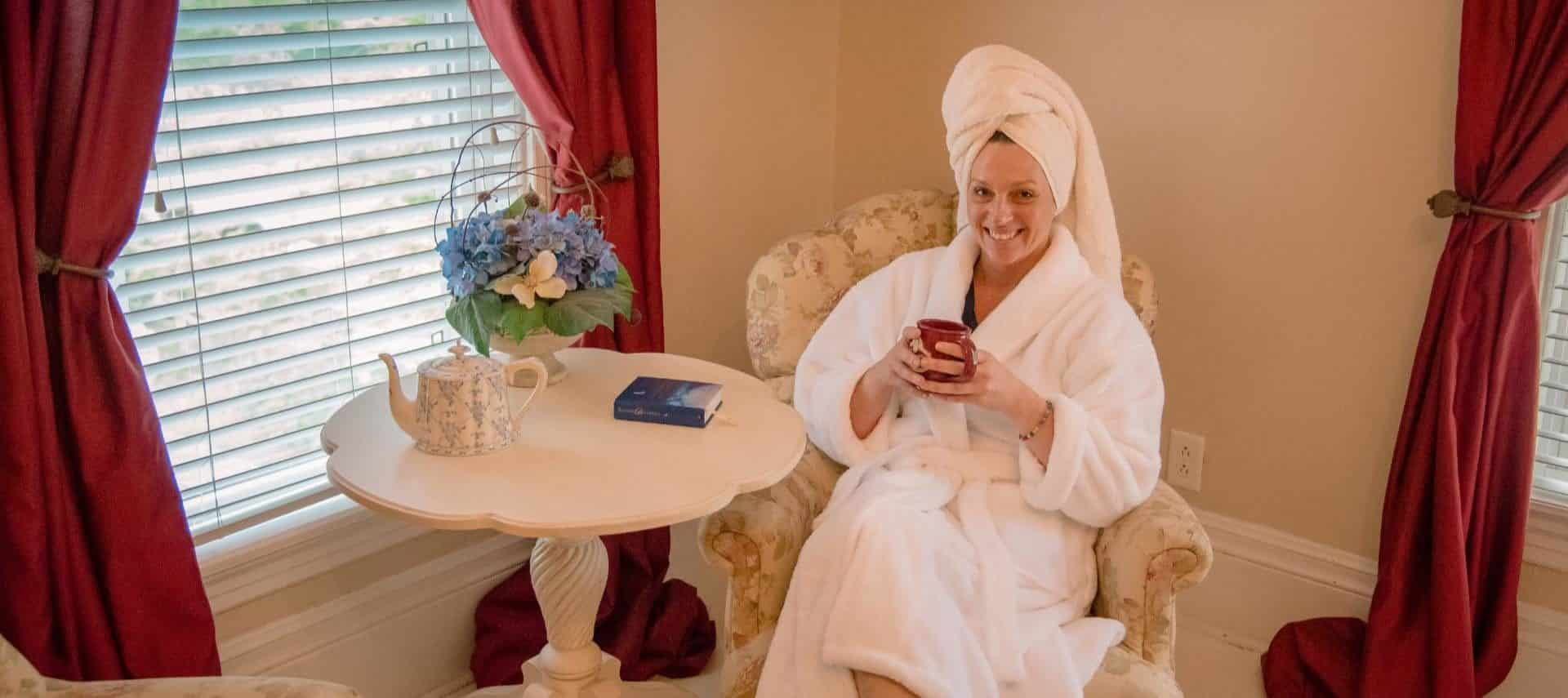 Woman in white robe with white towel on head relaxing in a chair drinking a cup of coffee