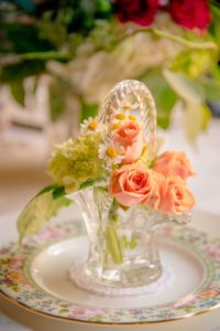 pretty crystal basket filled with roses sitting on a china plate