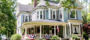 Front exterior view of the property painted blue and white with dark shutters, wrap around porch, American flags, and surrounded by green trees