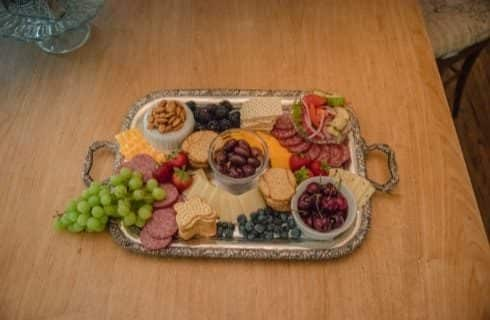 Metal tray filled with multiple types of fruit, cheese, crackers, nuts, and olives