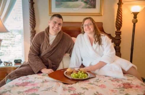 Man in brown robe and woman in white robe sitting on bed with a tray of fruit