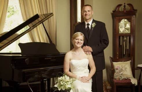Groom in black suit and bride in white dress next to black piano