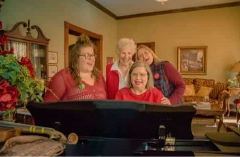 Four ladies smiling and singing songs around a piano