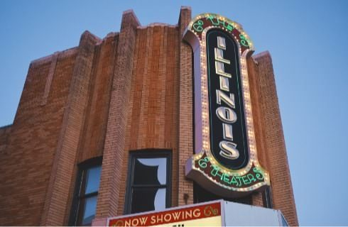 Close up view of large lighted sign at the top of a red brick building with a theater