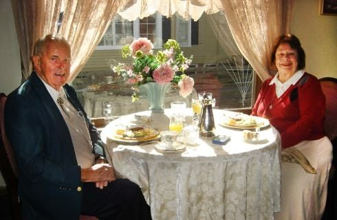An older gentleman and lady sitting at a nicely decorated table with a white table cloth and fresh flowers