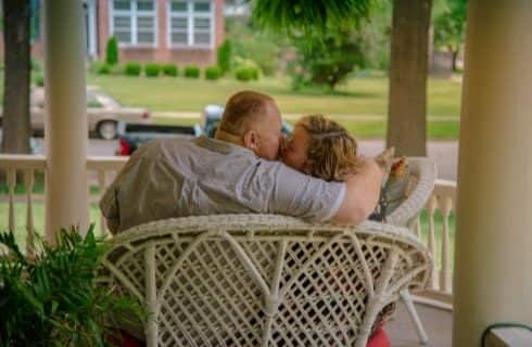 Man and wife kissing in a white wicker chair on the front porch