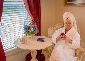 woman in fluffy white robe with white Turkish Towel on her head sitting in a side chair with a mug of coffee