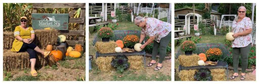 woman decorating an iron bench with pumpkins and mums